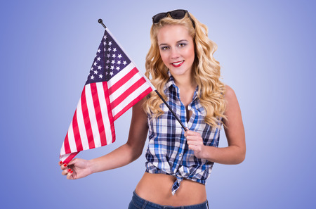 Caucasian woman holding american flag on blue gradient background photo