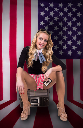 Caucasian retro woman sitting an old radio on american flag  photo