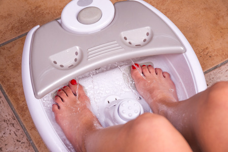 massager: Womans feet in a vibrating feet massager Stock Photo