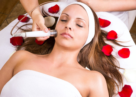 Woman getting laser and ultrasound face treatment in medical spa center, skin rejuvenation concept
