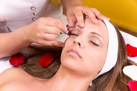 tweezing eyebrow: Woman getting tweezing eyebrow by beautician.