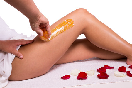 Sugaring: epilation with liquate sugar at legs. photo