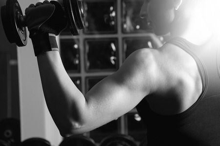 Young woman lifting the dumbbells photo