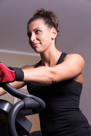 Woman smiling on exercise bicycle in the fitness room  photo
