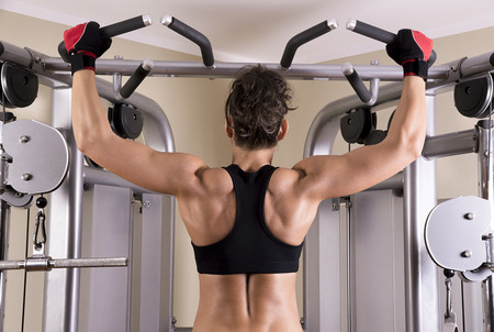 fat burning: Athletic young woman showing muscles of the back