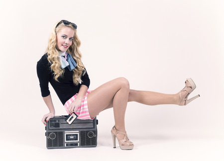 Pin up girl sitting on a retro radio. Vintage style. photo