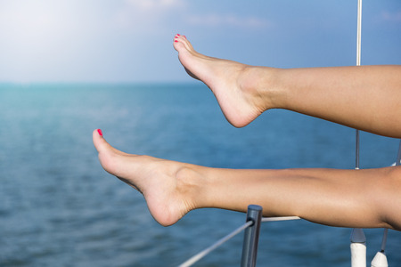 Closeup on beautiful sexy womens feet on the yacht photo