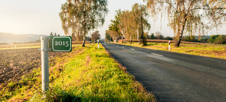 green signboard at the roadside in an autumn landscape. 2015 text. photo
