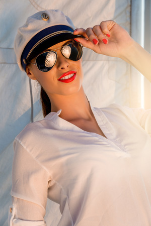 Adorable model wearing sea admirals hat and sexy top at sunset. photo