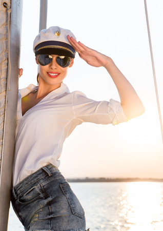 Adorable model wearing sea admirals hat and sexy top at sunset.