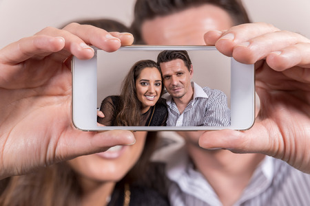 Caucasian couple taking a selfie  with mobile phone. photo