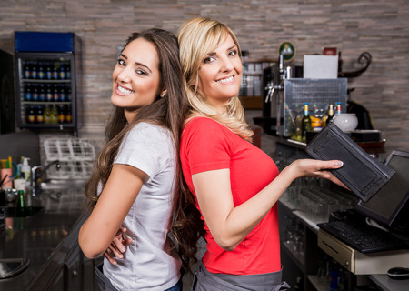 Two smiling waitress standing in a coffee shop
