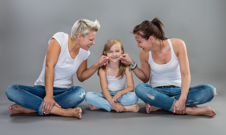 toothless: Two beautiful women making fun with a litte toothless girl. Stock Photo