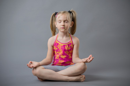 The little girl sits in a pose meditation 免版税图像