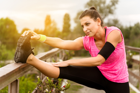 healthy exercise: Attractive young runner woman doing stretching exercises. Stock Photo