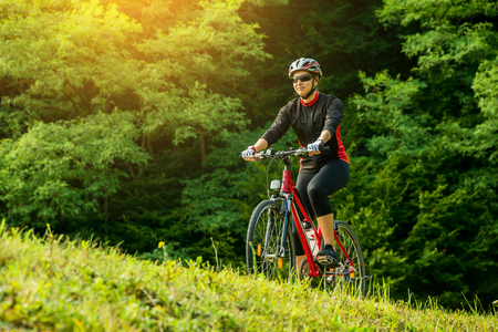 healthy sport: Young woman riding a bike in the forest at sunset.