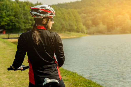 people in action: Young woman riding a bike at a beautiful lake.