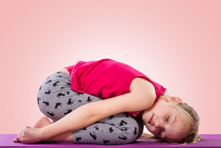 Little girl sitting in yoga pose over color background. Imagens