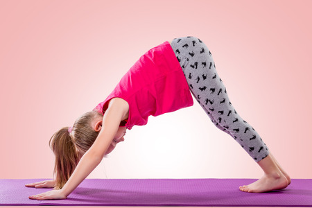 yoga pose: Little girl sitting in yoga pose over color background. Stock Photo