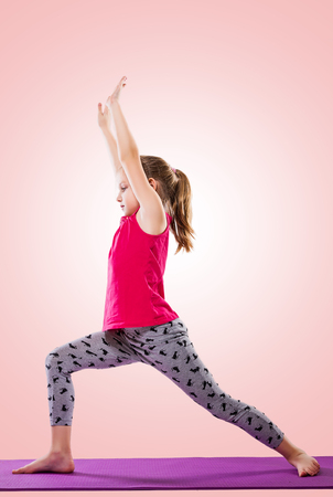 Little girl sitting in yoga pose over color background. Standard-Bild