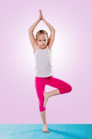 Little girl sitting in yoga pose over color background. Фото со стока