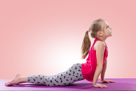 Little girl sitting in yoga pose over color background. Stock Photo