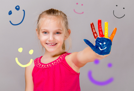 kids painted hands: Colorful painted hands in a beautiful young girl. Stock Photo
