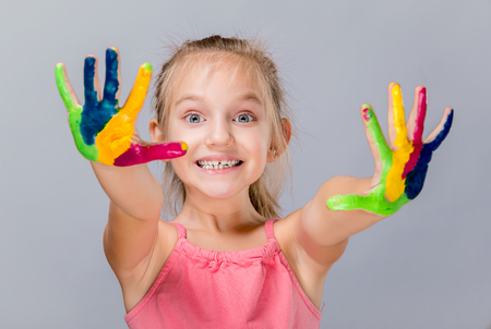 painted hands: Colorful painted hands in a beautiful young girl. Stock Photo