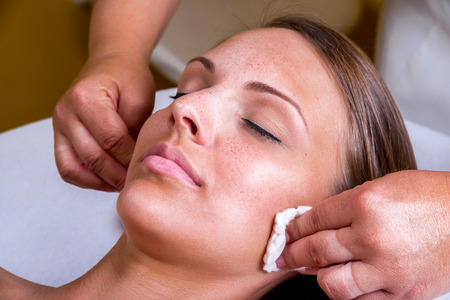 chemical peels: Freckles woman having a cosmetic treatment at the beauty salon. Stock Photo