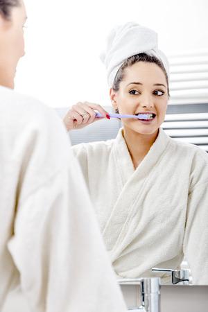 dientes sanos: Mujer agradable que limpia sus dientes en el baño. Foto de archivo