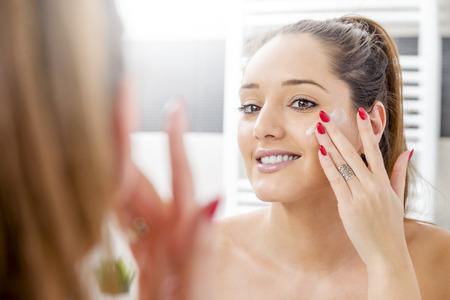 chica atractiva que pone la crema anti-envejecimiento en su cara