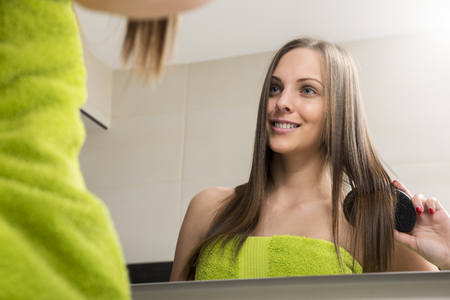 combing: Young woman combing her hair in bathroom at the morning. Stock Photo