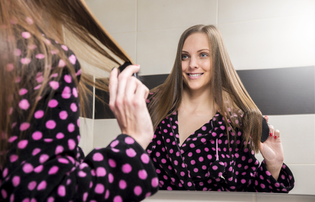 Young woman combing her hair in bathroom at the morning. Standard-Bild