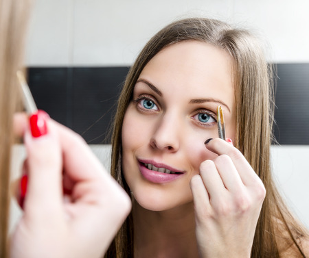 shaping: Beauty fresh model girl shaping eyebrows with tweezer
