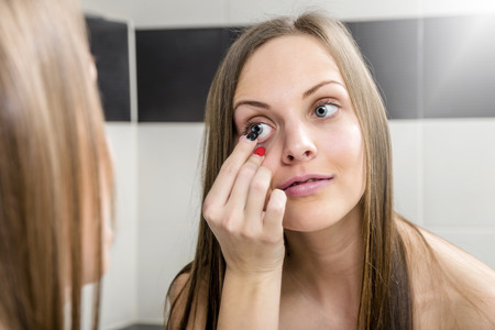 wearer: Young woman putting contact lens in her eye close up Stock Photo