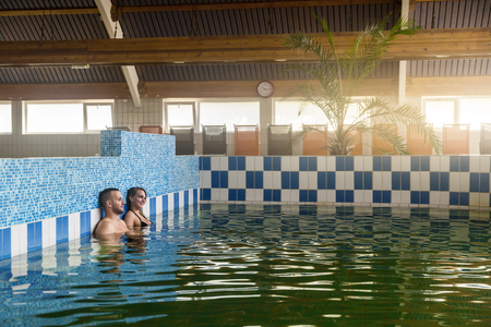 Young couple enjoying the thermal water in spa. Green water with healthy ingredients.
