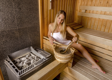 Young woman relaxing in sauna and enjoy the hot air.