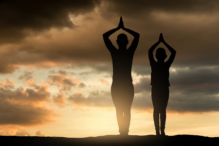 Silhouette of woman and her child doing yoga at sunset. Фото со стока