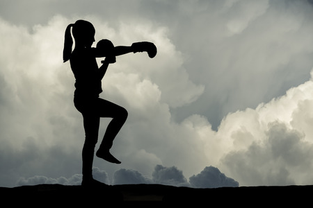 Young girl boxing at sunset. Silhouette series.