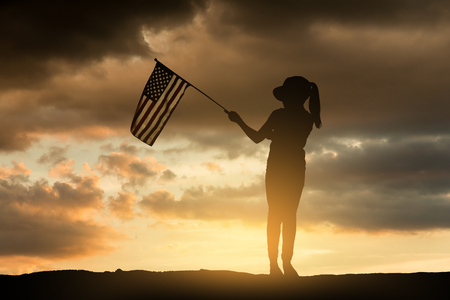 Young girl holding American flag at sunset. Silhouette series.