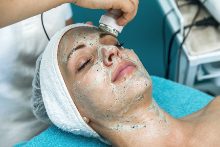 Confident young woman is enjoying cavitation skin care treatment at spa salon.