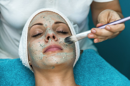 Cosmetician applying facial cream. Beautiful woman having a cosmetic treatment.