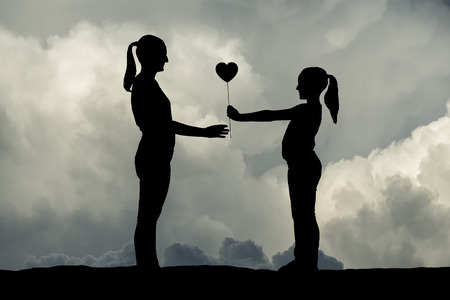 Child giving a heart to her mom in mother's day. Silhouette series.