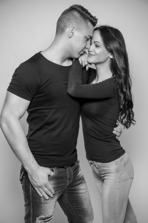 Black and white fashion studio photo of beautiful couple, embracing each other.