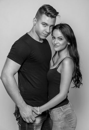 Black and white fashion studio photo of beautiful couple, wears elegant clothes, embracing each other.