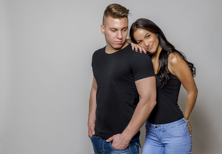 Fashion studio photo of beautiful couple, wears jeans clothes, embracing each other.