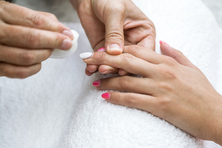 Beautician applying red varnish to finger nails. The process of painting woman nails with red and white lacquer close up. Standard-Bild