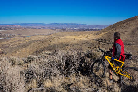 u s: Mountain Biker stops on an over look to take in the view of Reno Nevada