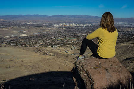 Woman Hiker sitting on boulder overlooking Reno Nevada on a sunny day photo