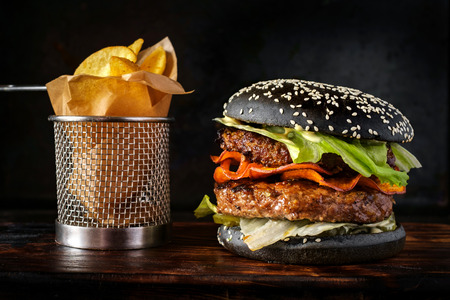 black Burger with two patties is on a wooden Board behind a black background next to the fried potatoes